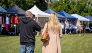 Crowd of people on grassy lawn with vendor tents at annual wine festival