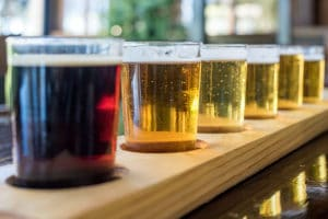 Beer samplers in small glasses individually placed in holes fashioned into a unique wooden tray at breweries and wineries.