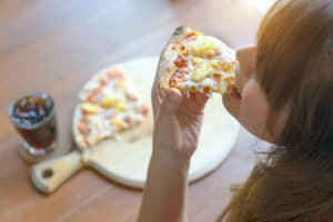 Woman Eating Tasty Pizza in great restaurants in independence