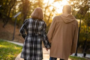Couple holding hands and walking in park during a Romantic Bed and Breakfast getaway